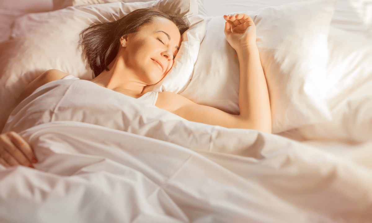 Woman sleeping in white sheets.